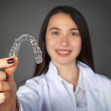 Woman holding up Invisalign tray