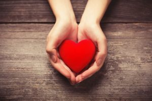 Heart in outstretched hands represents American Heart Health Month